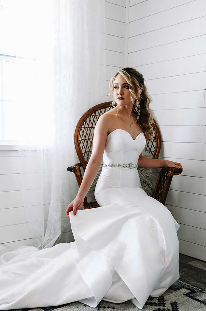 Bride sidding on a chair with hair and makeup done by Jennifer