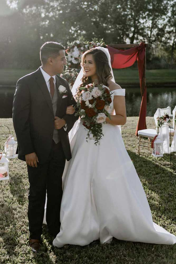 Groom escorting bride who is styled with Hollywood hair and glam makeup by Jennifer
