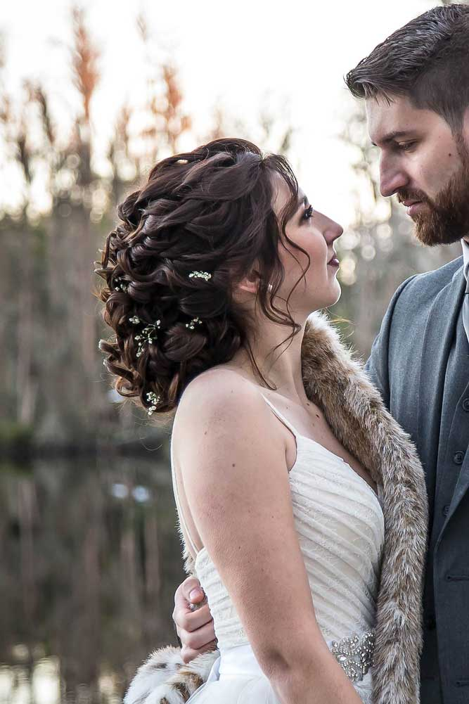 Bride looking up to groom with textured updo done by Jennifer